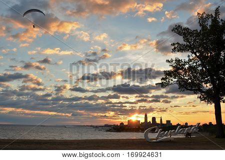 Sunrise view of Cleveland skyline, Lake Erie, and paraglider from Edgewater park