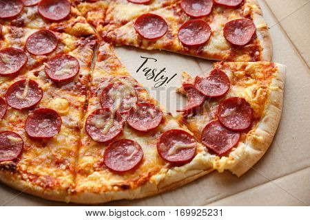 Bitten off a piece pepperoni pizza. Hot homemade food. Sliced fresh italian classic salami pizza. Popular topping with cheese. Baked meal.