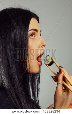 Young beautiful woman eating sushi over grey background