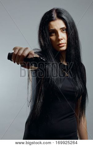 Pretty criminal girl posing with gun over grey background