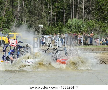 Naples Florida USA - March 3 2012: Swamp buggies pushing bow waves of muddy water