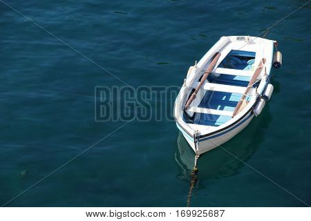 white-blue boat with two oars on still blue water