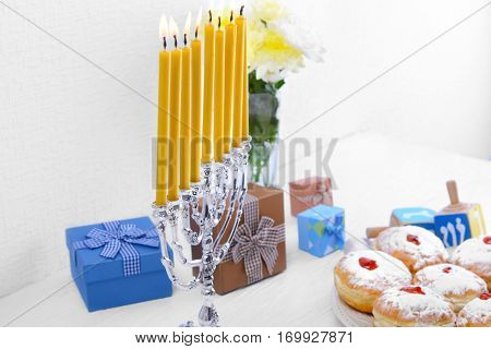 Beautiful menorah with burning candles for Hanukkah on wooden table against textured wall