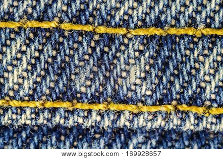 Macro image of blue jeans interwoven gold thread denim texture background