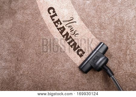 Vacuuming carpet with vacuum cleaner. House cleaning. Housework service. Close up of the head of a sweeper cleaning device.