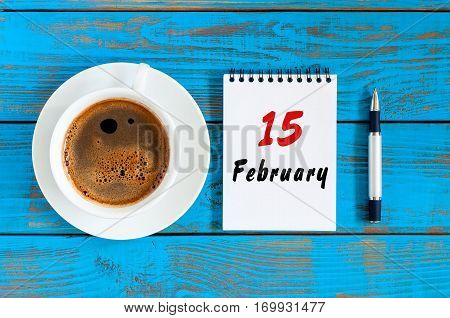 February 15th. Day 15 of month, Top view on calendar and morning coffee cup at workplace background. Winter time.