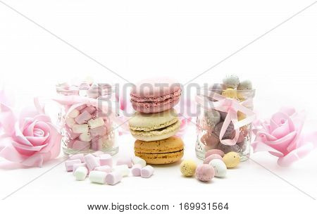 Easter Treats with eggs marhmallows macaroons and pink roses on a white background