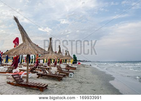 The Black Sea Shore, Sea Side With Sand, Umbrellas, Sun Beds And Water, Blue Sky