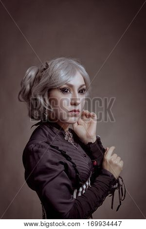 Old-fashioned lady with black eyes posing over grey background