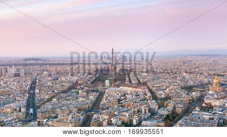 Aerial panoramic view of Paris skyline with Eiffel Tower, Les Invalides and business district of Defense at pink sunset, as seen from Montparnasse Tower, Paris, France