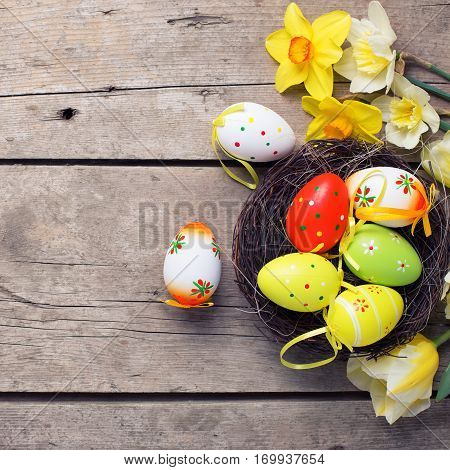 Easter background. Fresh yellow tulips and daffodils flowers decorative eggs in nest on vintage wooden background. Selective focus. Place for text. Square toned image.