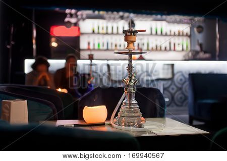 Close-up photo of transparent hookah on bar background.