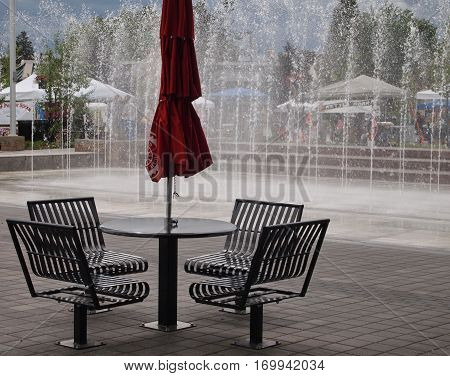 An outdoor cafe style table and chairs with a fountain in the background at a city park in Central Oregon with the dark sky of a looming storm on a summer day.