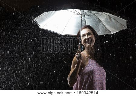 Beautiful woman with pink dress standing in rain under an umbrella at night