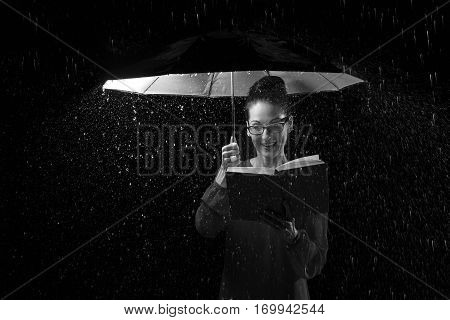 Beautiful woman with dress reading a book in rain under an umbrella