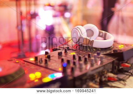Mixing console with headphones at the night club.