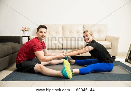 Hispanic Young Couple Stretching Together