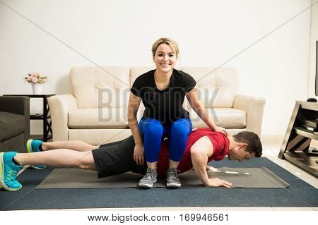 Woman Helping Boyfriend Do Some Push Ups