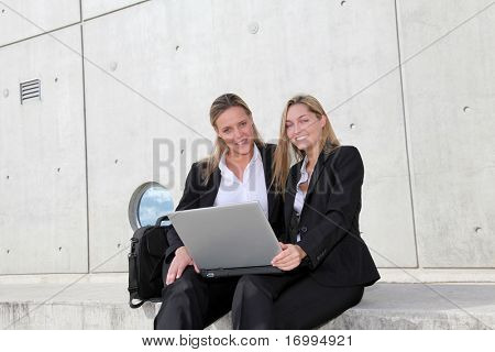 Women working on laptop computer in front of concrete building