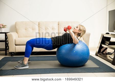 Woman Lifting Weights And Using Stability Ball
