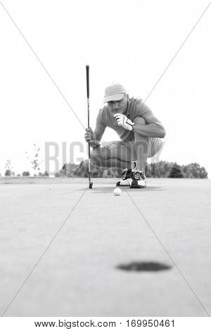 Middle-aged man looking at ball while crouching on golf course