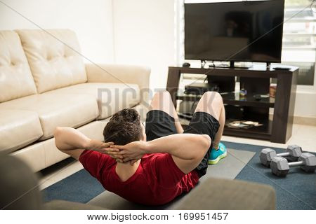 Man Following An Exercise Routine On Tv