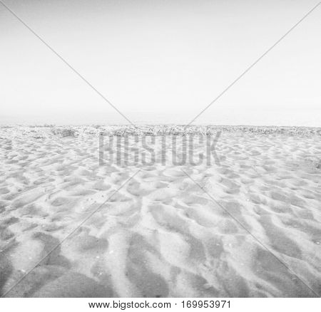 Abstract artistic background texture of sunny yellow golden sand beach and cloudless blue sky in fairy paradise with water, light white mirage and illusion, black, gray toned, space perspective view