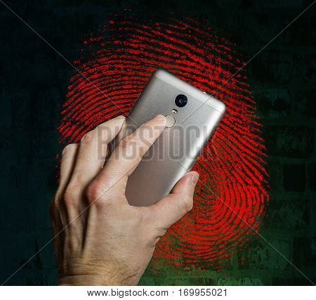 Finger touches the fingerprint scanner on the smartphone against a fingerprint on brick wall