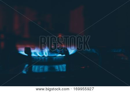 lit burner on the gas stove in the dark