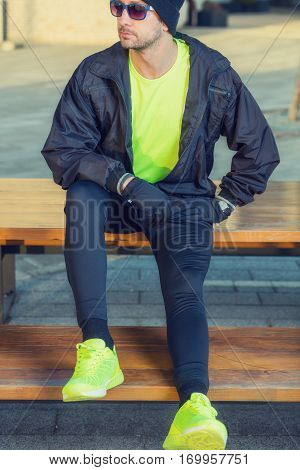 Urban jogger making pause on a bench.