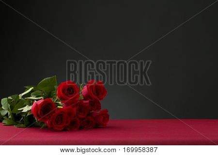 red roses boquet over red table with dark background