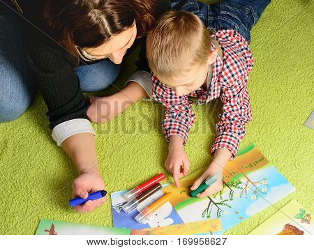 the child together with mother draws a picture lying on a green carpet