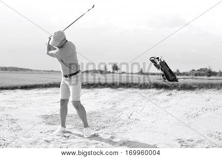 Man swinging at golf course against sky