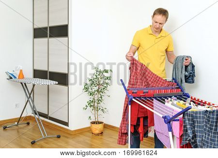 The man takes off things from drying rack clothes.