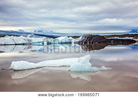 Morning in the Ice Lagoon, Iceland. Drift ice Ice Lagoon - Jokulsarlon. Icebergs and ice floes are reflected in the smooth water surface. The concept of extreme northern tourism