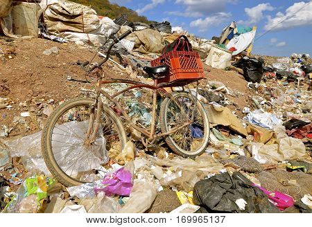 Trash, litter, and garbage in a city dump surround an old bicycle