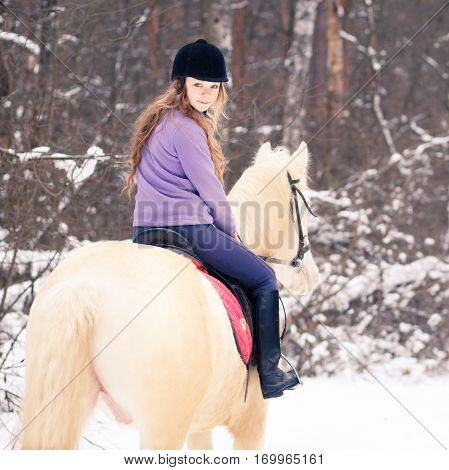 Young rider girl in helmet on albino horse in winter forest