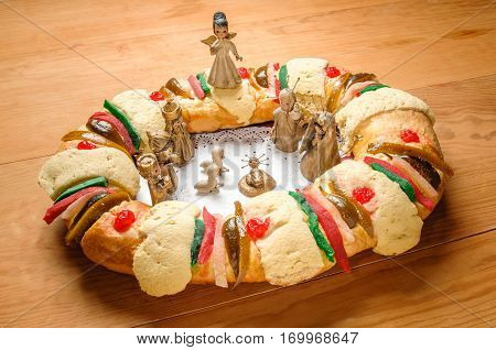 Epiphany Cake kings cake or Rosca de reyes with manger on wooden table