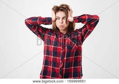 Young funny woman in plaid shirt making crazy face isolated on white background