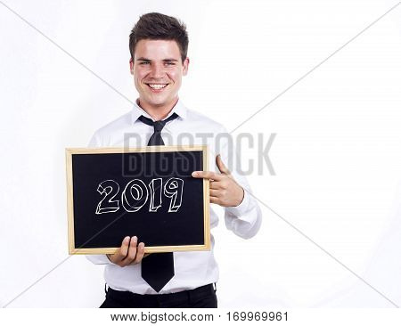 2019 - Young Smiling Businessman Holding Chalkboard With Text