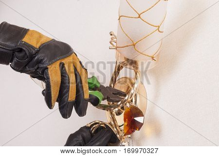 electrician with pliers in his hand repairing a sconce