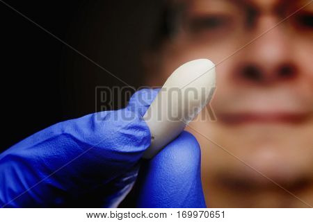 suppository in blue rubber glove closeup, shallow depth of field