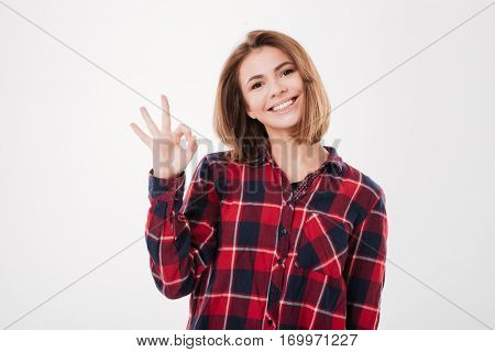 Smiling cheerful girl in laid shirt showing okay sign isolated on a white background