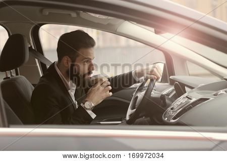 Guy with beard driving and watching the radio