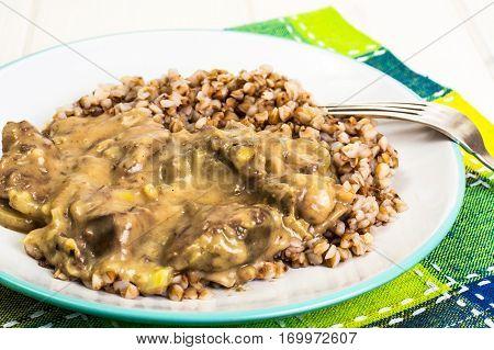Meat with gravy, buckwheat on plate. Studio Photo
