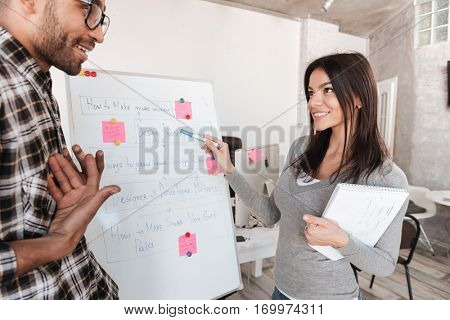 Image of young cheerful business couple in office working with flipchart. Look at each other.