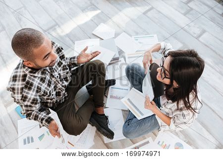 Top view photo of happy business partners in office working with documents on floor.