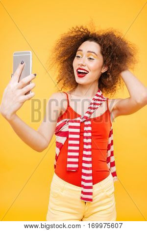 Vertical image of Bright model making selfie on phone. Isolated orange background