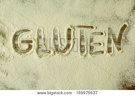 Flour on the table with writted word GLUTEN