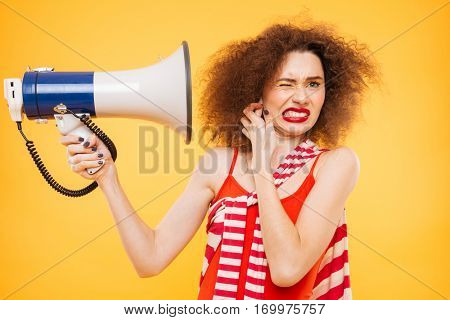Bright model with megaphone. Woman covering by the megaphone. Isolated orange background